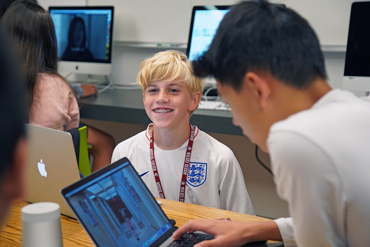Students working at computers with one boy smiling at the camera