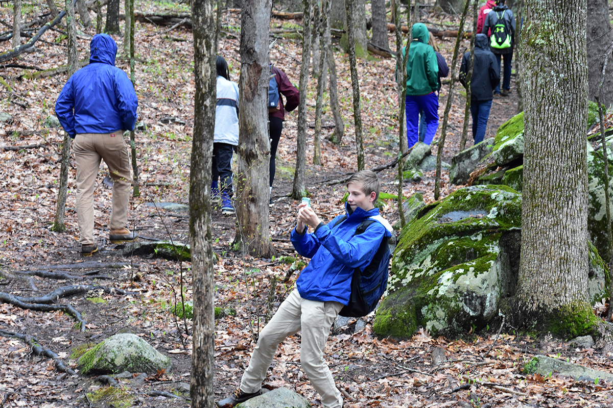A student snaps a photo during a hike through the Lubberland Creek Preserve in Newmarket.