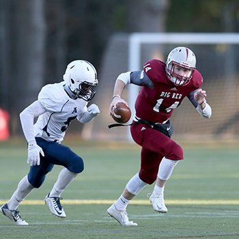 An Exeter football player eludes a tackler inside Phelps Stadium
