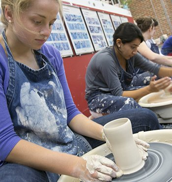 Two students work with clay on pottery wheels.