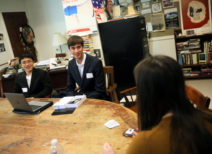 Exonians Harrison He '21 and Evan Chandran '21 polish their pitch for a startup with mentor Emma Butler, a senior at Brown University, during the Emerging Entrepreneur Initiative.