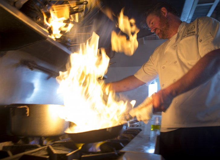 Chef Jason Goodenough working at a stove with flaming food.