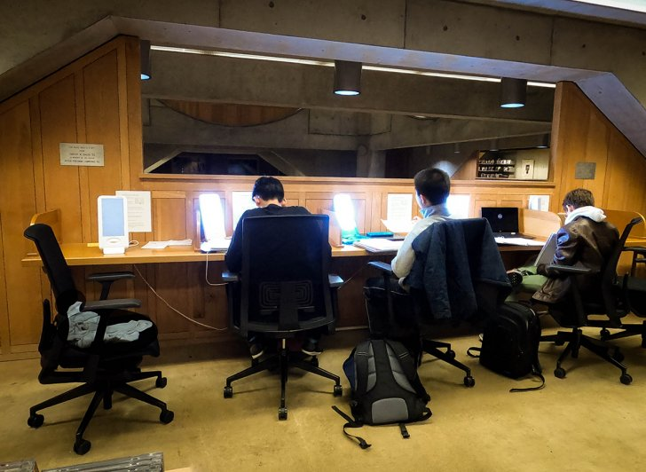 Three students sit in front of light therapy lamps in the Academy Library.