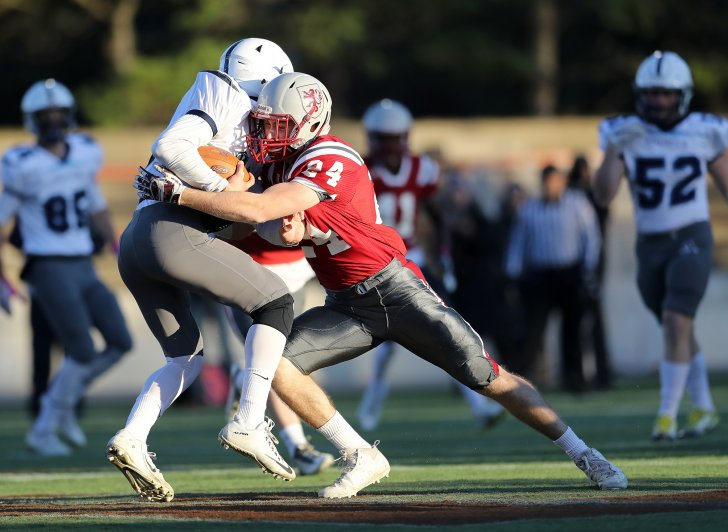 Exeter football player tackles an Andover player at E/A games.