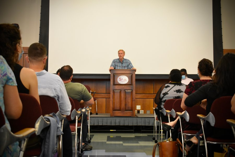 Principal Bill Rawson stands on the dais as he addresses the opening faculty meeting of the new school year.