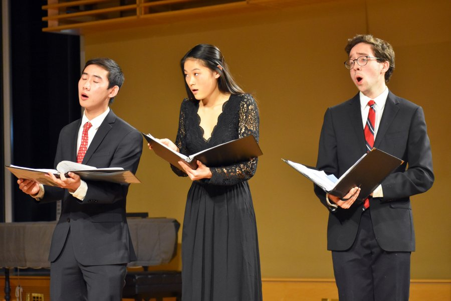 Three Exeter students singing during a performance.