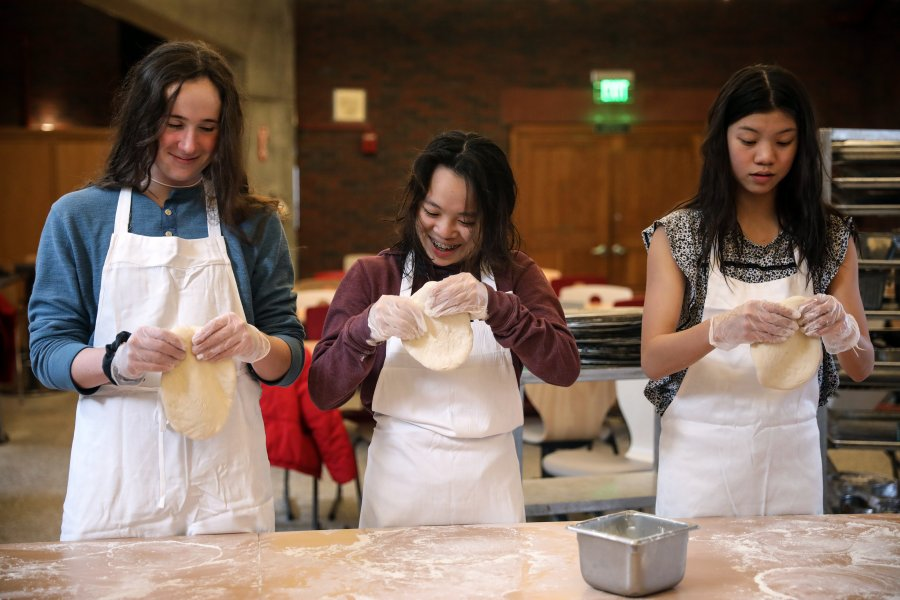 Three students working with pizza dough.