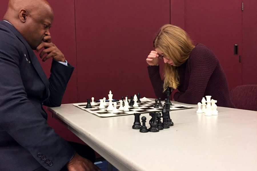 Chess Grandmaster Maurice Ashley (left) and Katya Davis '20 study the chess board in the last math of a 10-board simultaneous competition Thursday night, Jan. 8, 2020.