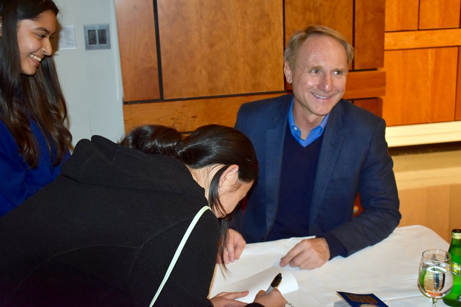 Dan Brown '82 signs books after speaking with the class of 2023.