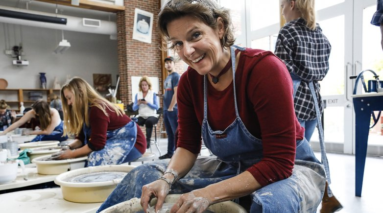 Mother uses pottery wheel in art class.