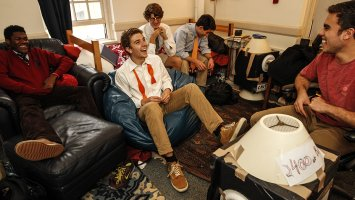 Boys laughing in a dorm room.