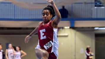 Girl track athlete takes off in the long jump event