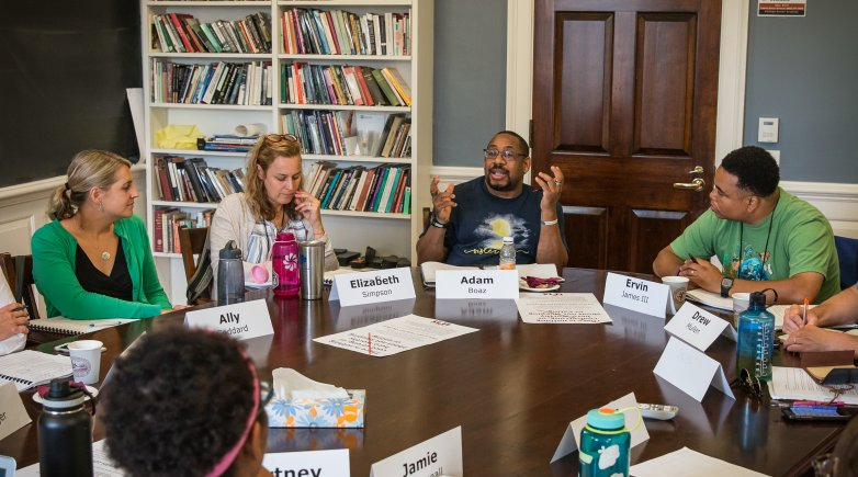 Educators hold a discussion around the Harkness table during the 2018 Exeter Harkness Institute.