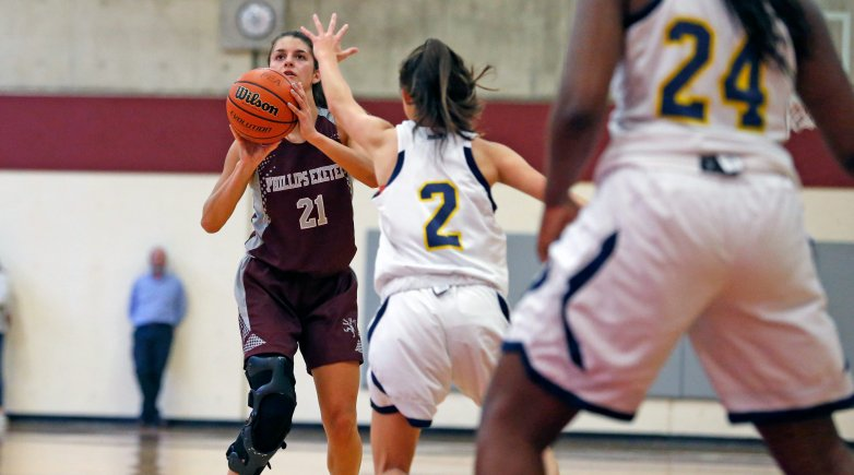 Bethany Lucey on the basketball court about to score.