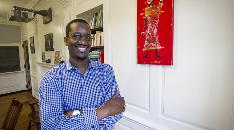 Amadou standing next to a Senegalese painting in his classroom.