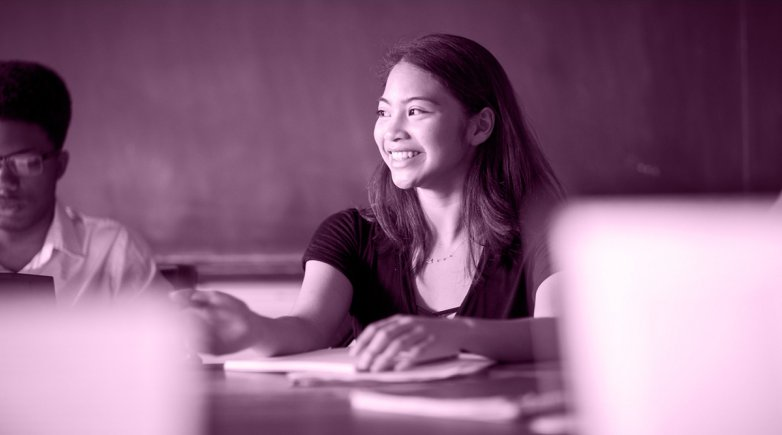 Exeter student seated at a Harkness table and smiling