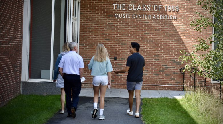 A student guides a prospective family on a tour of campus.