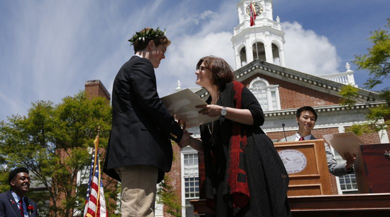 Student shakes Principals Lisa MacFarlane's hand while accepting his degree.