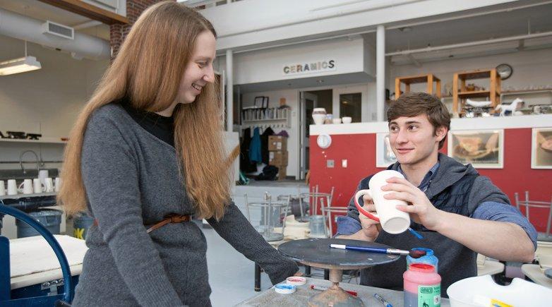 Carla Collins smiles as a student as he applies glaze to a ceramic mug
