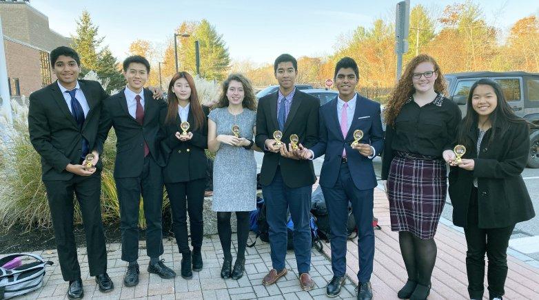 Members of Exeter's debate team standing outdoors.