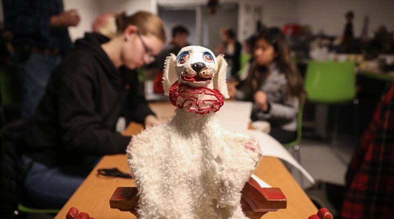 A dog puppet on a table with students working in the background.