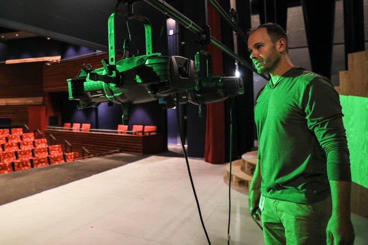 Jake Josef adjusting a row of lights on stage.