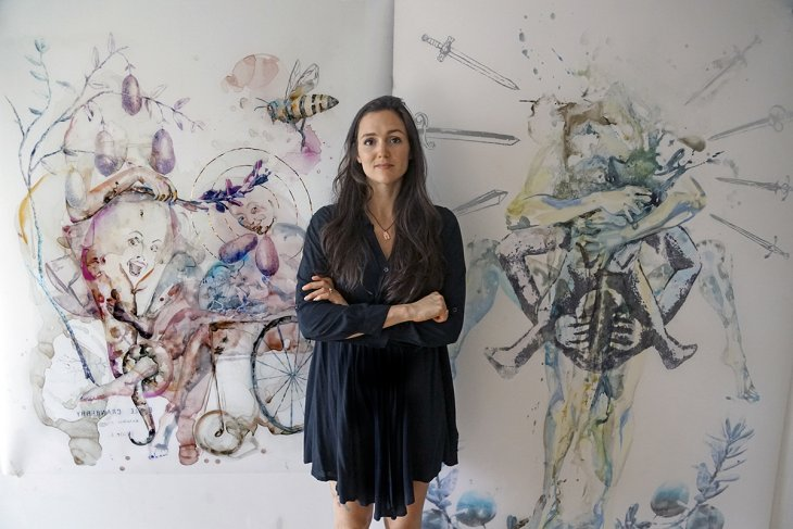 Alexandra Carter poses in front of two of her paintings