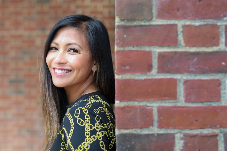 Sherry Hernandez leaning against a brick wall and smiling