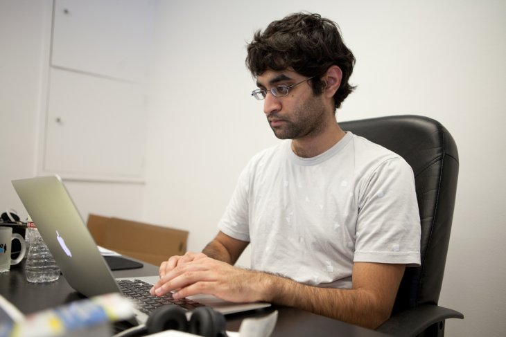 Exeter graduate Kush Patel in front of a computer