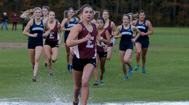 Girl cross country runner leads the pack through standing water.