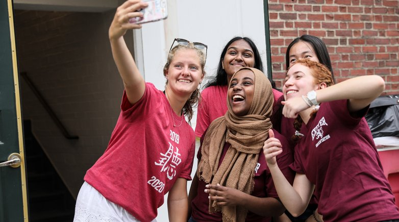 Exeter proctors take a selfie with a new student moving into the dorm.