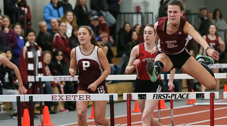 An Exonian athlete grimaces with effort as she takes the lead at the hurdles.